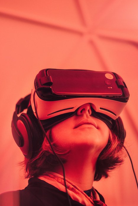 Pink toned portrait of a girl looking through virtual reality viewer - future of photography predictions