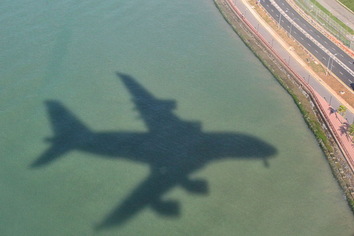 The shadow of an airplane in flight on water