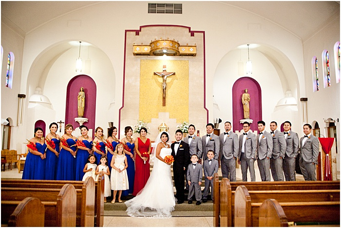 A group photo of a wedding party posing in a church - wedding flash photography