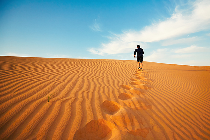 Young man is running to the top of dune in desert.