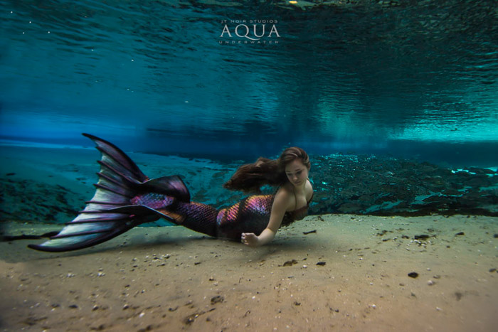 A magical underwater mermaid photoshoot featuring a female model with mermaid tail swimming underwater