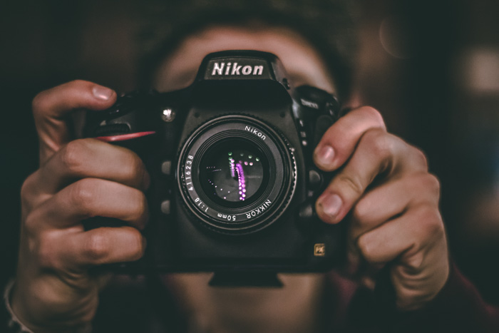 A portrait of a photographer holding a mirrorless Nikon camera