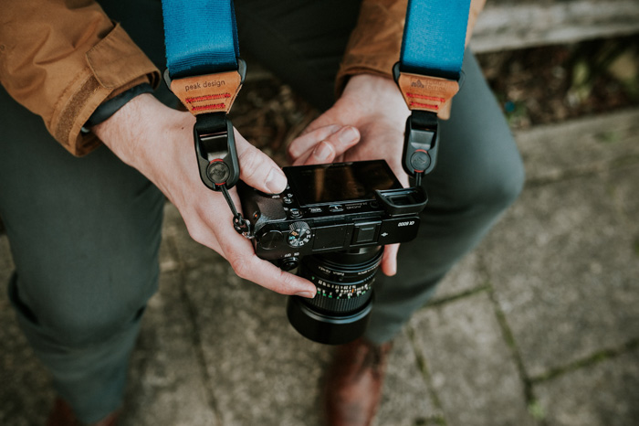 A close up of a photographer checking settings on a mirrorless camera