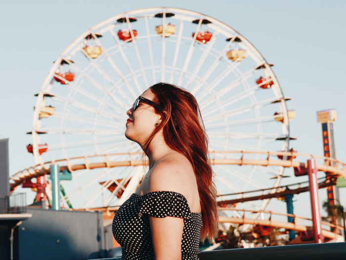 An outdoor portrait of a girl posing in front of a ferris wheel shot with a mirrorless camera
