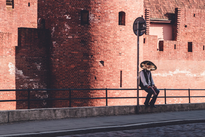 A man in a sombrero sitting on a fence outside a red brick building - mirrorless camera history