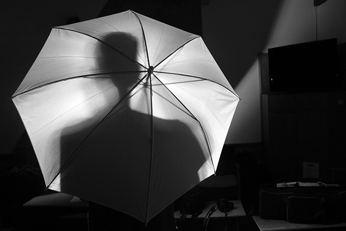 Monochrome shot of the silhouette of a person behind an umbrella