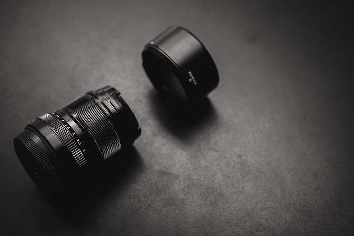 Flat lay of a camera lens and lens hood resting on dark background - photography business equipment