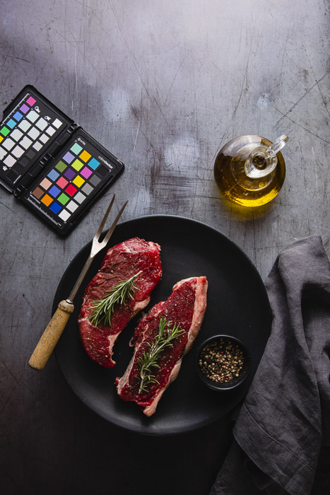 Food photography still life including a plate of raw meat, olive oil and color checker - photography business equipment