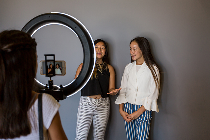 Two female models being photographed in a freelance photographers home studio setup