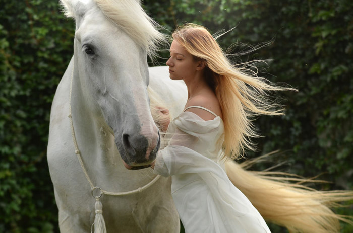 A dreamy photo of a female model with long blond hair posing beside a white horse
