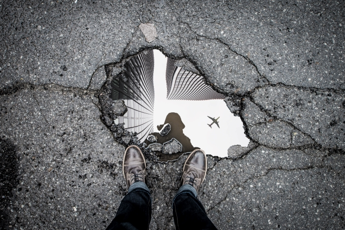 Reflection of an airplane and buildings in a puddle