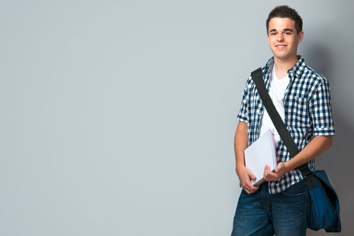A school portrait of a Smiling teenager with a schoolbag standing on wall background - tips for quality school portraits
