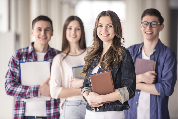 A Group of happy young students in a university posing with books - school portraits tips