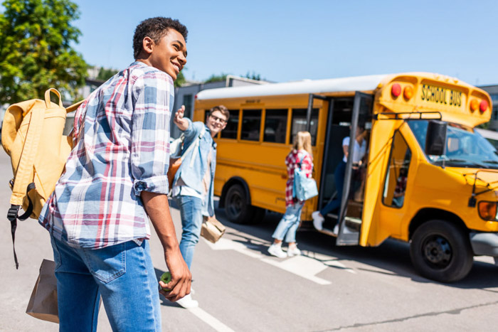Students boarding a yellow school bus on a clear day - school portraits tips