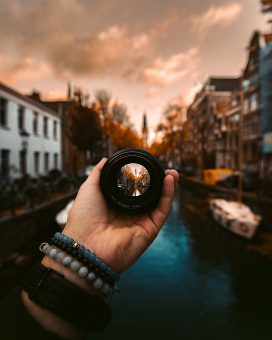 A close up of a person holding a camera lens over a stunning canal scene at sunset