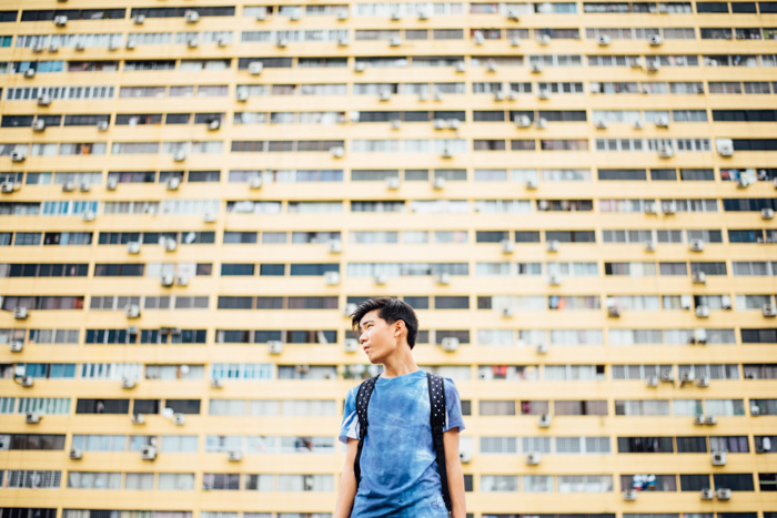 An outdoor portrait of a male model posing in front of a multi windowed building shot using selective focus