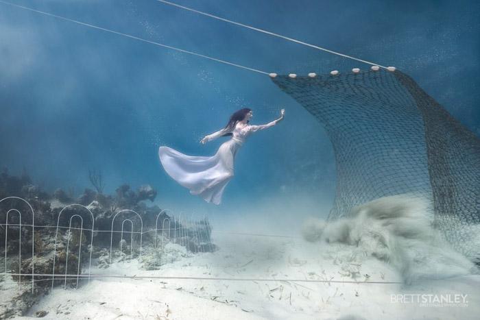 Dreamy underwater portrait of a female model swimming towards a net