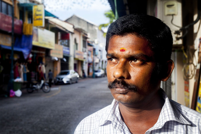 A close up portrait of a man standing on the street