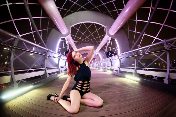 An urban photoshoot of a female model posing on a bridge under neon lights