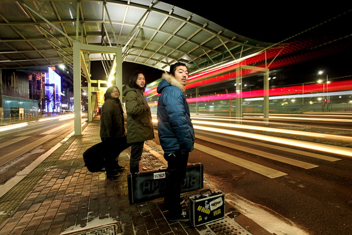 Urban portrait of three people waiting for public transport at night