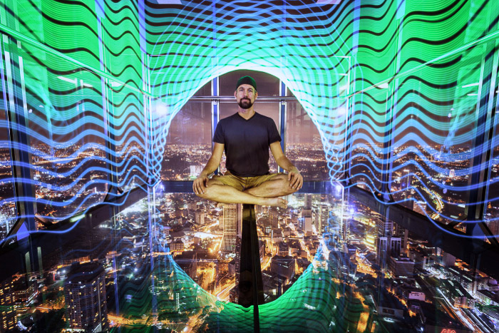 A surreal urban portrait of a man levitating over a night cityscape surrounded by neon lights