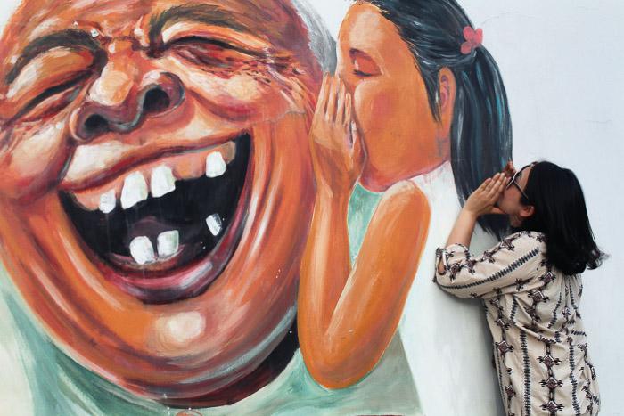 Urban portrait of a female model posing by wall graffiti