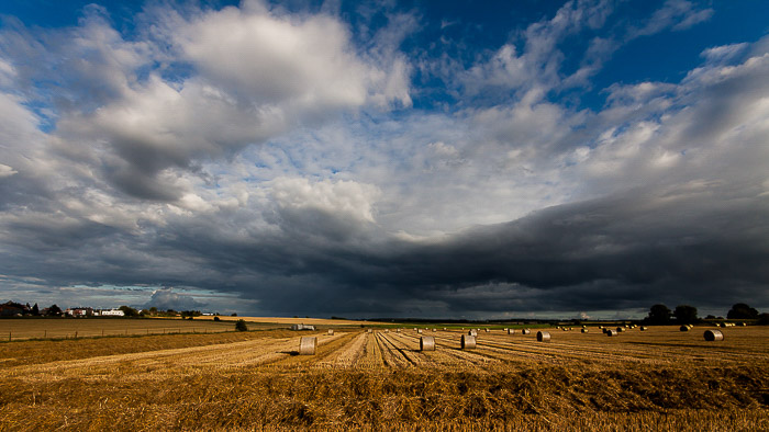 A typical wide angle landscape shot of a field under a cloudy sky