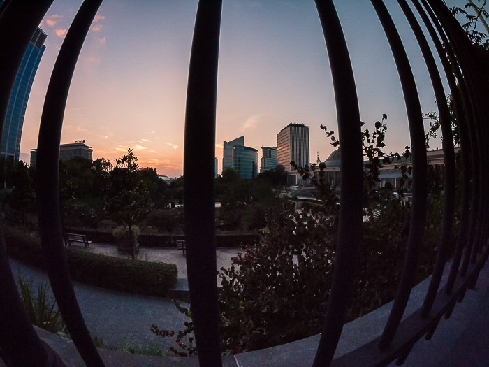 A cityscape shot through fence railings in low light, demonstrating lens distortion from using a fisheye lens