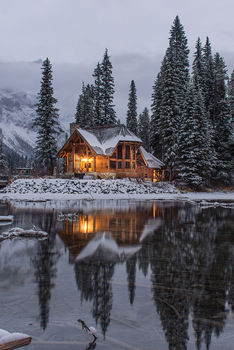 A beautiful architectural shot of a building behind a lake in the snow - winter photography ideas
