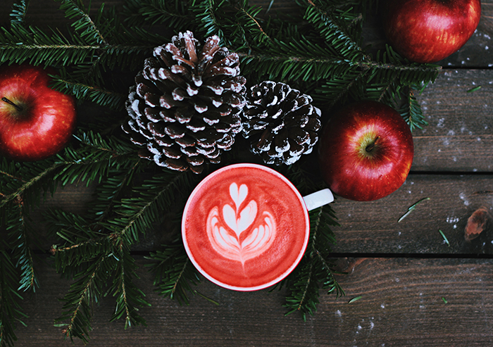 A Christmas-themed flat lay featuring apples, pine cones, tree branches and latte art - winter photography ideas