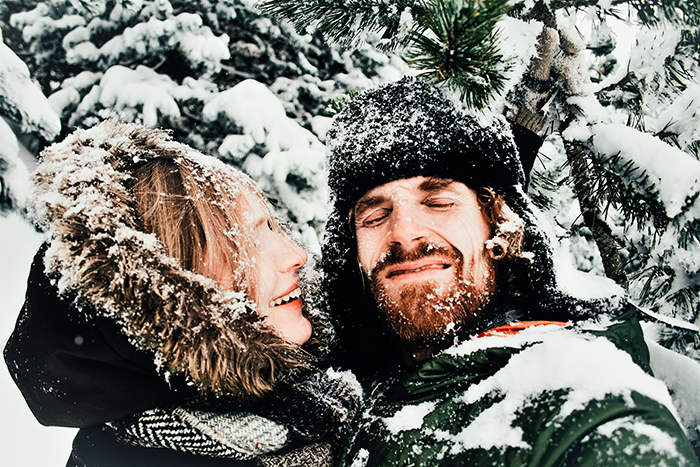 Humorous snow portrait of a couple posing casually - winter photography ideas