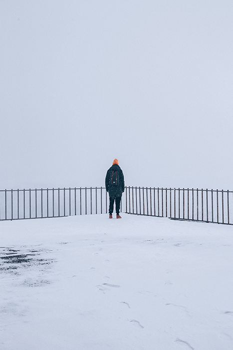 A snowy winter portrait of a figure standing by a fence