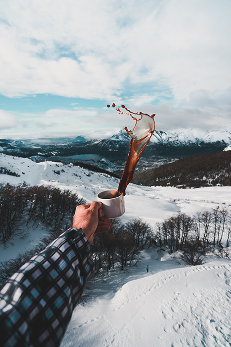 Creative photo of a man holding a coffee cup with a splash towards a snowy winter landscape