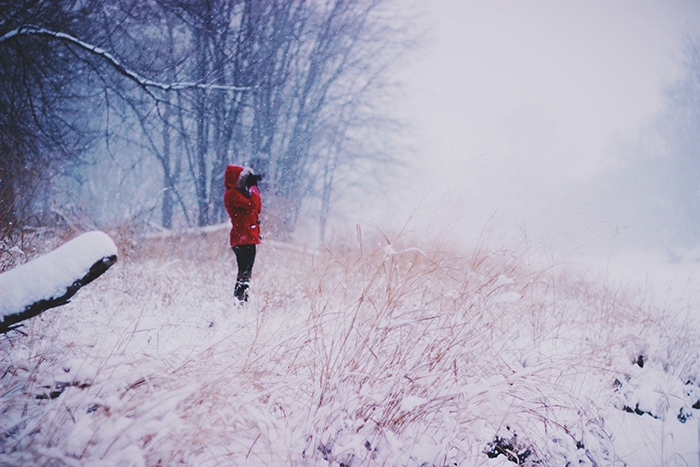 A female model standing by a forest in the snow - winter photography ideas