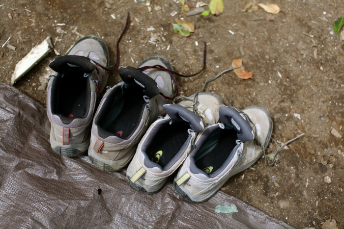 Overhead shot of two pairs of sports shoes on a campsite ground during an adventure photography trip