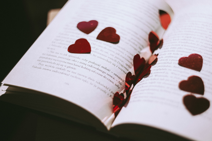 Artistic still life of heart shaped confetti scattered on the pages of a book - fine art wedding photography