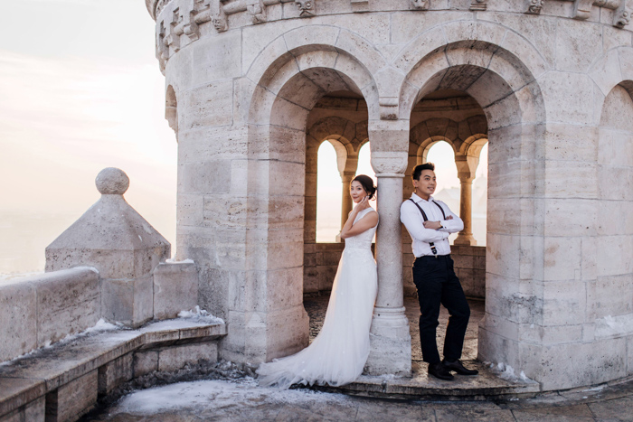 Artistic portrait of a newlywed couple posing in the tower of a classical building - fine art wedding photography
