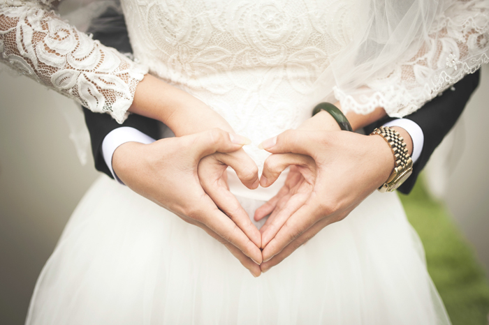 Artistic close up portrait of a newlywed couple holding each others hands in a heart shape - fine art wedding photography