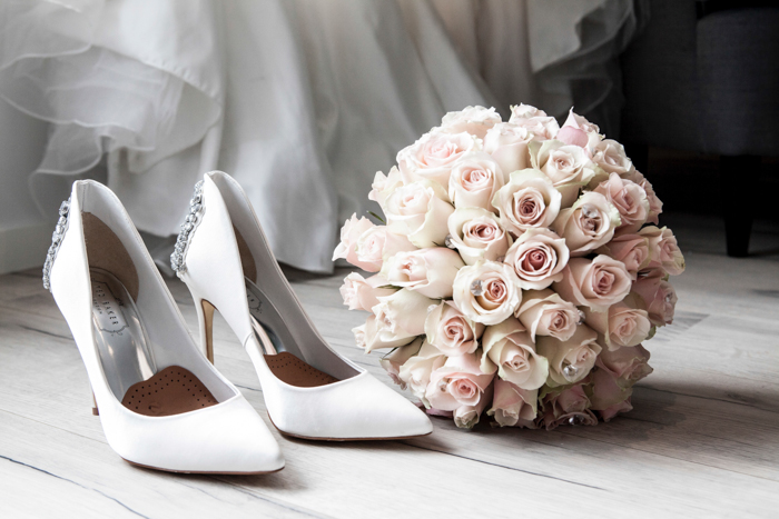 Artistic still life of a wedding bouquet and shoes on wooden floorboards - fine art wedding photography