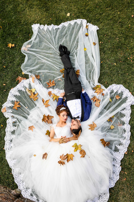 Artistic overhead shot of a newlywed couple lying on the grass - fine art wedding photography
