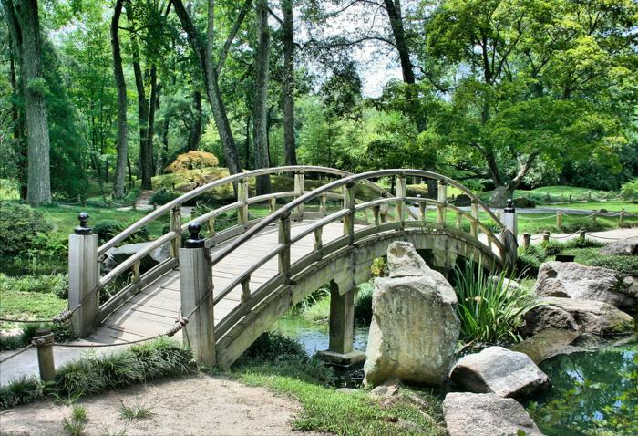 A wooden bridge in a pretty Japanese garden