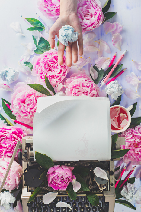 Cool still life featuring roses, a typewriter and a hand holding crumpled paper - spring photography ideas
