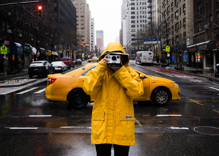 A photographer in a yellow mac shooting outdoors in front of a yellow taxi cab in the rain - cool spring photos