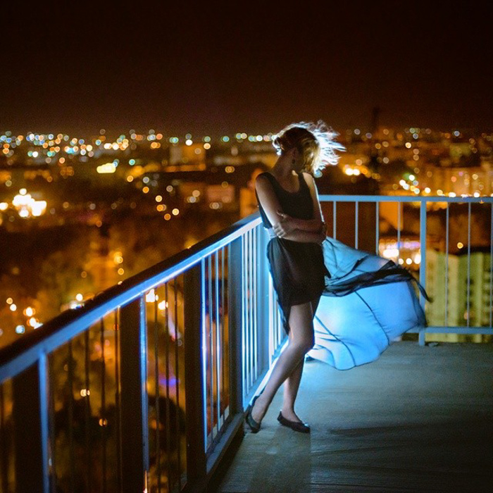 Stunning portrait of a female model posing on a balcony at night shot with a speedlight
