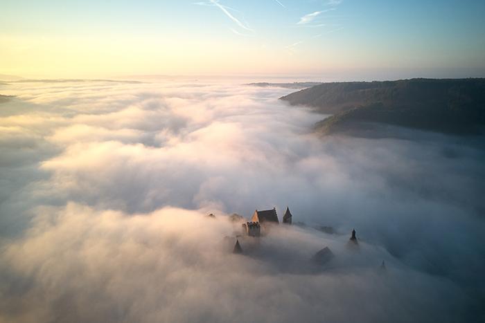 foto de um castelo cercado por nuvens