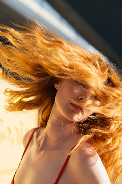Stunning portrait of a girl tossing her auburn hair - beautiful photography principles