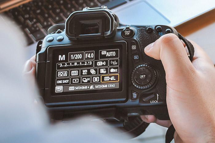 a photographer adjusting burst mode settings on a DSLR camera