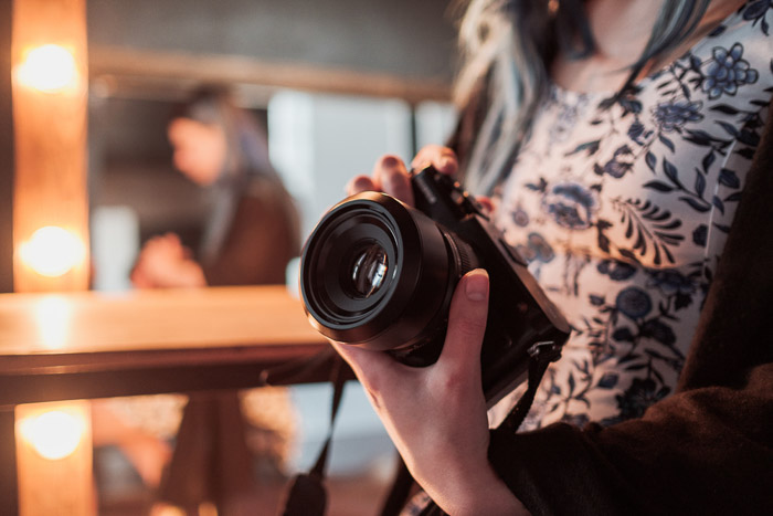A candid shot of a woman holding a DSLR camera indoors