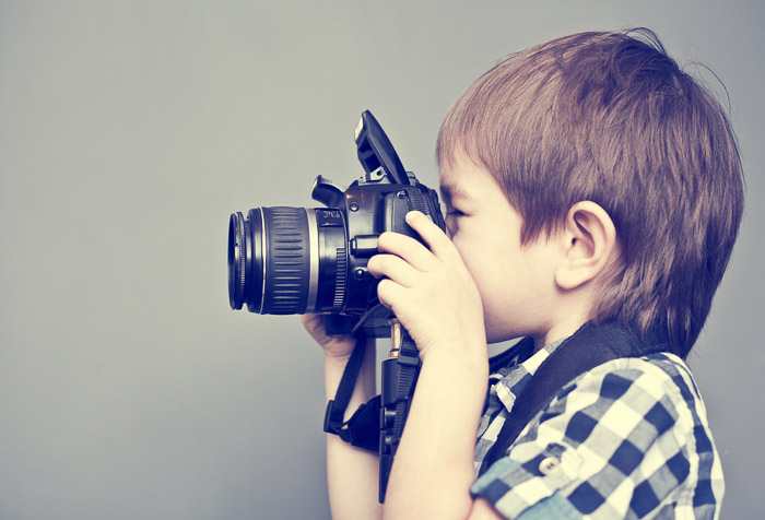 Sweet portrait of a young boy holding a DSLR camera