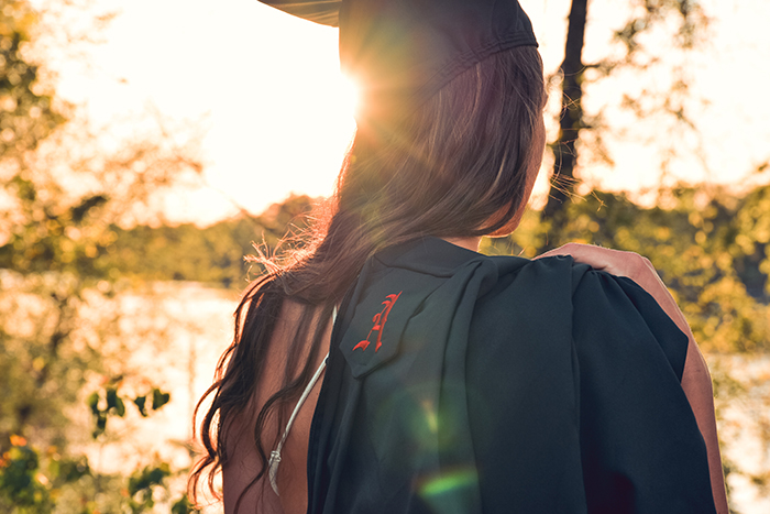 Beautiful candid graduation portrait of a female student outdoors in a forest